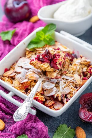 Plum crumble with oatmeal, almond flakes in a bowl close up on a dark textured background, selective focus. Stock Photo - 129374485