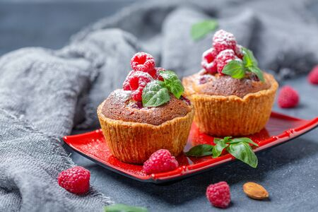 Plate with raspberry tartlets with almond cream filling and sprinkled with powdered sugar on linen cloth, selective focus.