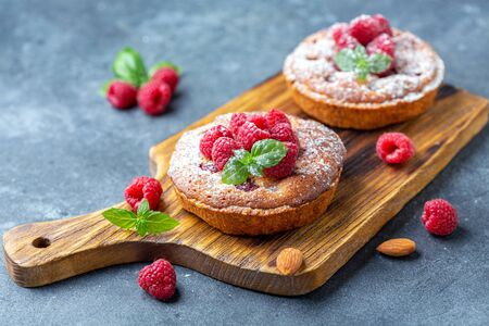 Tartlets with almond cream and fresh raspberries on a wooden serving board, gray textured background. Selective focus.