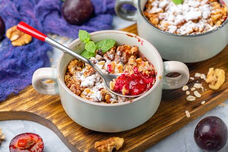 Cherry plum crumble dessert with oatmeal, vanilla, walnut crumb and mint in ceramic pans on wooden serving board close up, selective focus. Stock Photo - 129374793