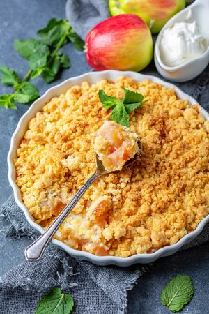 Apple crumble with cinnamon and a dessert spoon in a ceramic form on a dark linen cloth, selective focus.