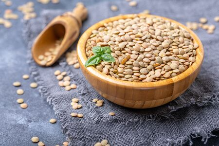 Brown lentil beans in a wooden bowl and a small scoop on grey linen homespun, selective focus.