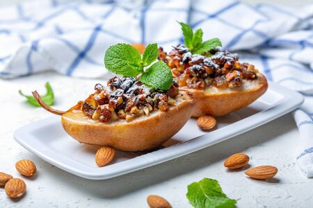 Pears baked in honey with nuts and raisins are served with green mint on a white plate, a selective focus.