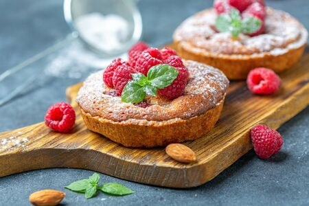 Delicious raspberry mini tarts (tartlets) with almond cream and green mint on a wooden serving board, selective focus.