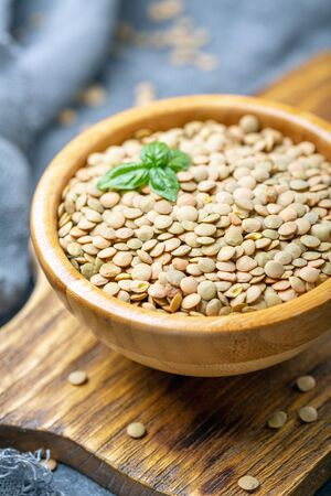 Organic brown dried lentils in a bowl on a wooden serving board, selective focus. Healthy vegan vegetarian food concept.