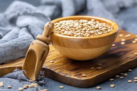 Bowl of brown lentils and a wooden scoop on a textured dark background, selective focus. Stock fotó