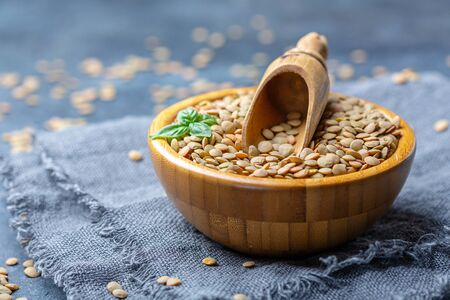 Brown lentils vegetarian food in a wooden bowl on linen homespun, selective focus. Stock Photo