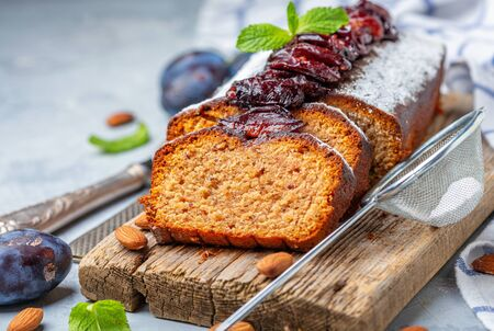 Delicious plum cake with spicy plums sliced on a wooden serving board, selective focus. Stock Photo