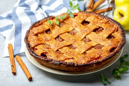 Homemade lattice apple pie with cinnamon on an old textured background with linen cloth, selective focus.