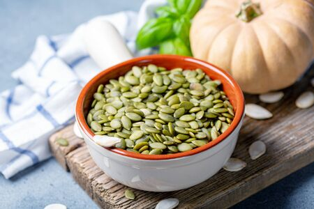 Raw pumpkin seeds in a ceramic bowl and the fruit of the pumpkin on old wooden board, selective focus.