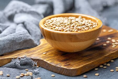 Wooden bowl of brown lentils on a textured dark background, selective focus. Standard-Bild - 133702485