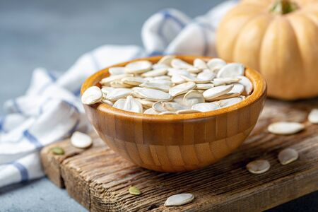 Bowl of raw pumpkin seeds on an old wooden board, selective focus.