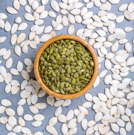 Peeled raw pumpkin seeds in a wooden bowl on a scattering of unpeeled pumpkin seeds.Top view, flat lay. Stockfoto