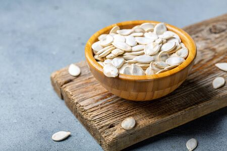 Bowl of organic pumpkin seeds on an old wooden board, selective focus. Stockfoto