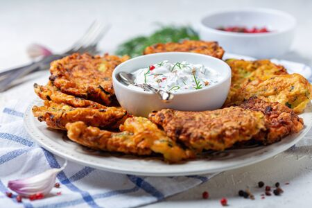 Zucchini fritters with yogurt sauce with greens, garlic and pink pepper on a white plate on a textured white background, selective focus. Standard-Bild - 133702813