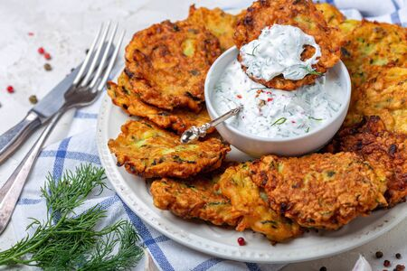 Zucchini fritters with yogurt sauce with greens, garlic and pink pepper on a white plate on a textured white background, selective focus. Standard-Bild - 133702822