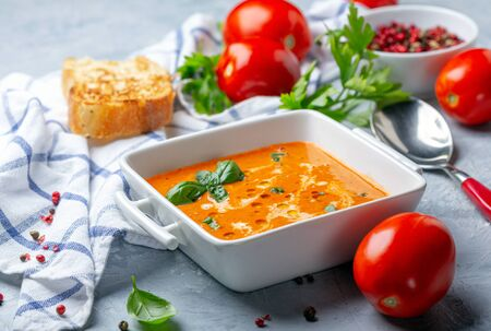 Homemade tomato soup with green basil, cream and olive oil in a bowl on a textured gray background, selective focus. Standard-Bild - 133702825