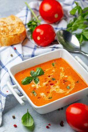 Fresh homemade tomato soup with a sprig of basil in a saucepan on a grey textured background, selective focus. Standard-Bild - 133702830