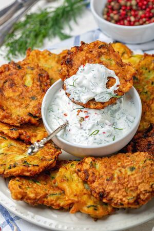 Zucchini fritters with spicy yogurt sauce are served on a ceramic dish on a homespun linen cloth. Standard-Bild - 133702831