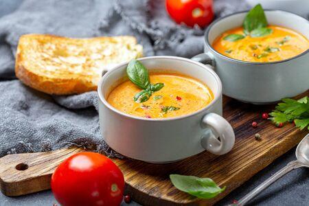 Deliciosa sopa de tomate con especias y albahaca verde en una olla de cerámica sobre un tablero de madera, enfoque selectivo.