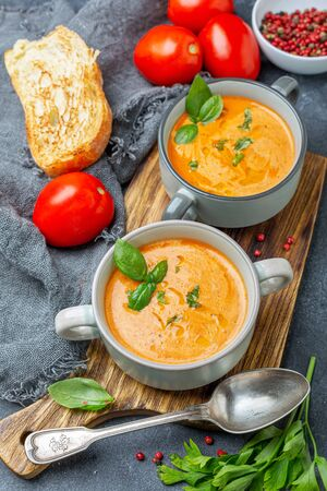 Homemade soup of fresh tomatoes, onions, garlic and herbs served with green basil in ceramic pots on a wooden serving board, selective focus. Standard-Bild - 133702840