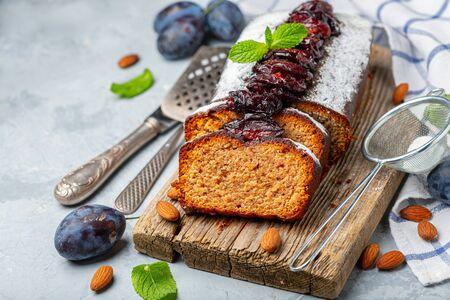 Delicious plum cake with spicy plums sliced on a wooden serving board, selective focus. Copy space.