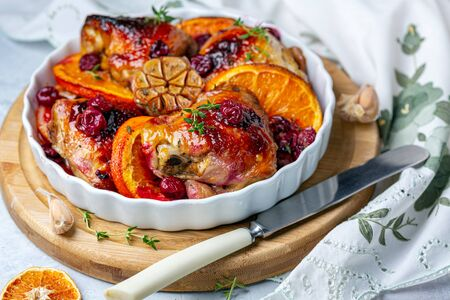 Chicken thighs baked with oranges, cherries and fresh thyme ceramic form on wooden serving board, selective focus.