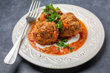 Homemade meatballs with tomato sauce and sour cream in a plate on a dark textured background.