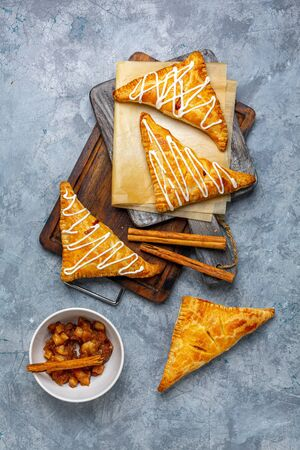 Homemade turnovers with apple filling and cottage cheese cream are served on a wooden serving board, with a textured concrete background. Top view, flat lay.