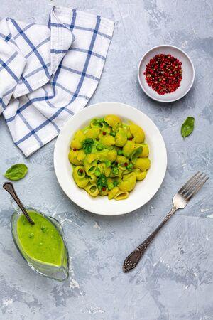 Pipe Rigate pasta with green pea cream sauce. Italian pasta recipe.Top view, flat lay.