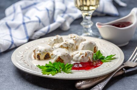 Swedish meatballs in a creamy lingonberry sauce with fresh parsley are served in a porcelain plate on a dark textured background, selective focus. Stockfoto