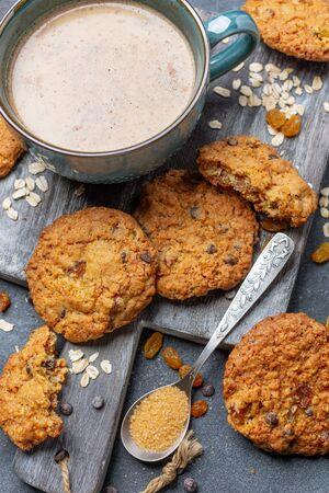 Biscuits à l'avoine faits maison avec des raisins secs et une tasse de café sur une planche de bois, vue de dessus. Nourriture pour le petit déjeuner.