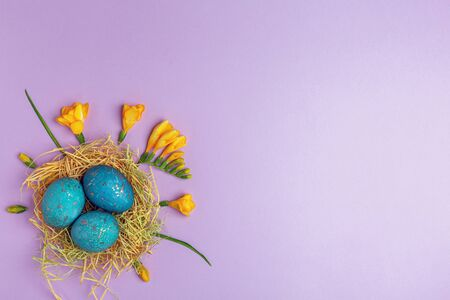 Easter background with eggs painted with natural dyes and yellow flowers. Top view, flat lay. 스톡 콘텐츠