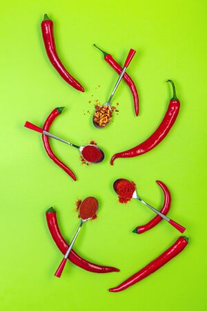 Background with different types of hot pepper and ripe red pepper pods. Top view, flat lay.