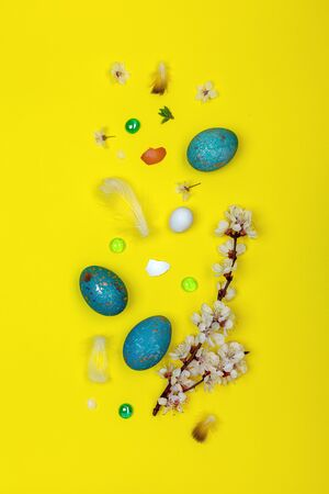 Easter blue eggs colored with a decoction of red cabbage and a flowering branch on yellow background. Top view, flat lay.
