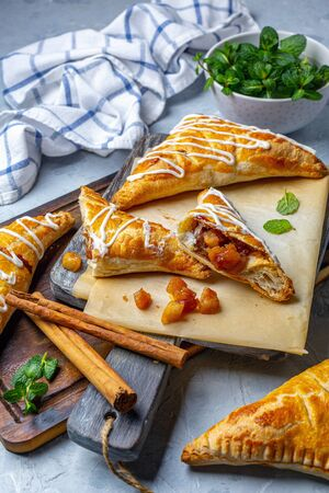 Apple turnovers and cinnamon sticks on a wooden serving board, selective focus. Stock Photo