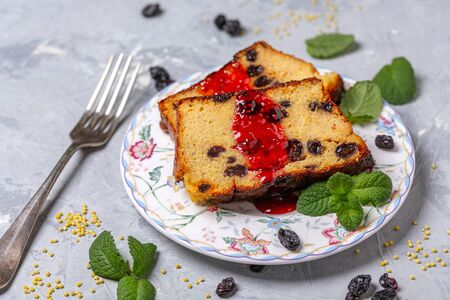Slices of homemade millet Kugel with raisins, served with fruit sauce and a sprig of mint, selective focus. Stockfoto