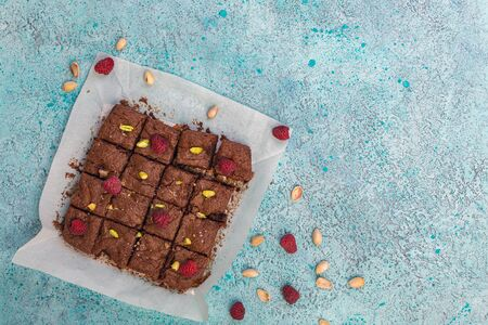 Traditional brownies made of dark chocolate with raspberries, sea salt and pistachios cut into pieces on a sheet of parchment. Top view, flat lay.