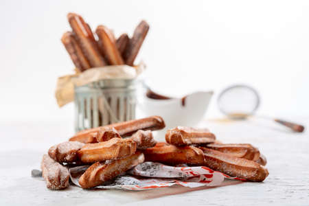 Churros sprinkled with sugar and cinnamon on a piece of newspaper, selective focus. 免版税图像