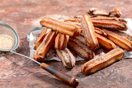 Churros sprinkled with sugar and cinnamon on a piece of newspaper, selective focus. Imagens