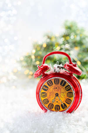 Christmas card with a red alarm clock on a snow-covered background with fir branches with lights.Copy space. Selective focus. Winter holiday, Christmas, New Year. Stock Photo