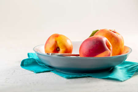 Fresh peaches on a blue plate. Stock Photo