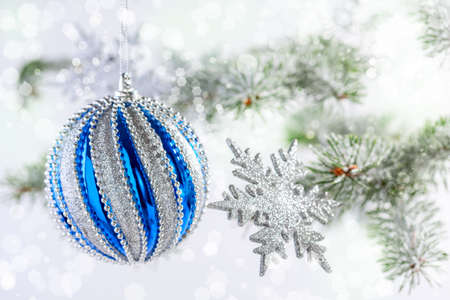 Blue Christmas ball, silver snowflakes and snow-covered fir branches close-up, selective focus. Christmas or winter concept. Stock Photo