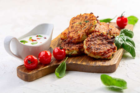 Zucchini fritters served with hot yogurt sauce, caramelized tomatoes and green basil, selective focus. Concept of healthy homemade food.