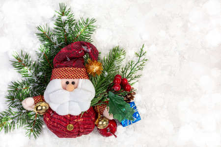 Santa Claus with bells and red alarm clock in the snow on the background of a Christmas tree with lights. Christmas concepts with copy space.