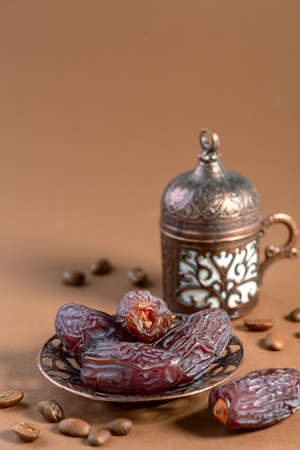 Dried dates are a popular dessert for Arabic black coffee in a traditional bronze dish, a selective focus. Still life with a copy of space.