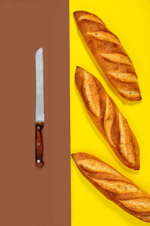 Freshly baked traditional baguettes and a bread knife on a contrasting two-color background with a copy of the space. Top view, flat lay.