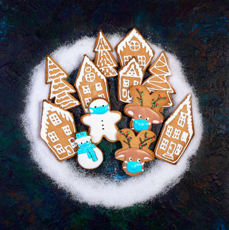 Funny ginger cookies in protective masks among gingerbread houses and fir trees. Concept of winter and Christmas holidays in the context of a pandemic. Flat lay, copy space.