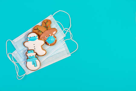 Christmas ginger snowmen and gingerbread houses and fir trees on a snowy blue background. Concept of winter and Christmas holidays. Flat lay, copy space.z Stock Photo
