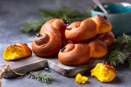 Scandinavian saffron and raisin buns are served on a wooden board, selective focus. Traditional Swedish Christmas pastries.